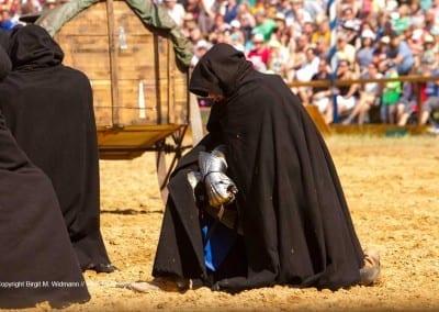 Ritter in schwarzem Mantel in der Arena